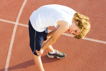 Young athlete bent over resting