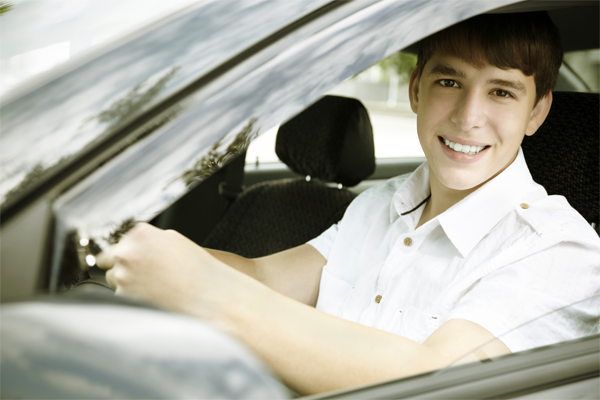 Teenage boy at the steering wheel of a car