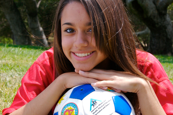 Smiling soccer player with chin resting on ball