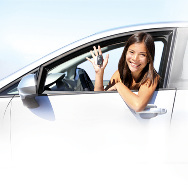 Smiling teen girl in driver's seat holding car keys
