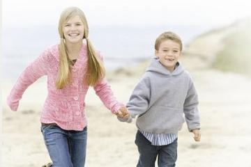 Smiling sister and brother holding hands at the beach