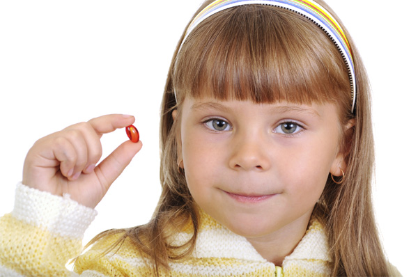 Young girl holding a pill