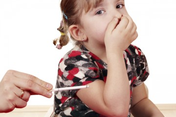 Little girl holding her nose with lighted cigarette near
