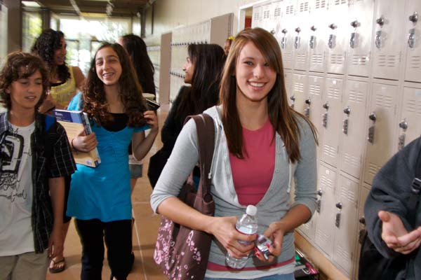 Smiling teen girl waling in the school hallway near the lockers