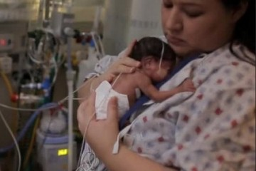Mom holding infant in the NICU