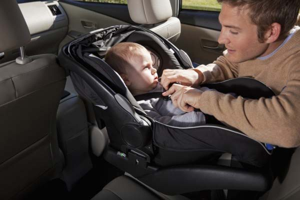 Father securing infant in car seat