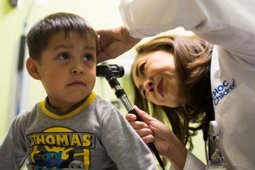 Pediatrician giving small boy health exam