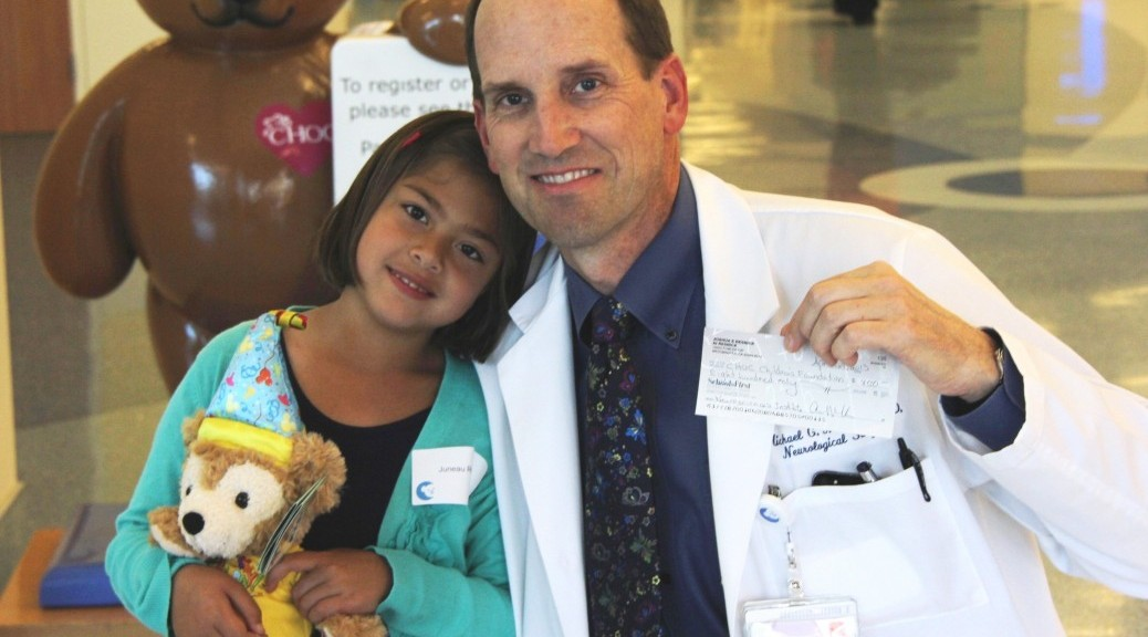 CHOC patient Juneau Resnick poses with Dr. Michael Muhonen, medical director of The CHOC Children's Neuroscience Institute