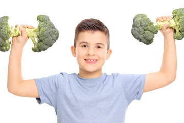Boy holding up broccoli like bar bells