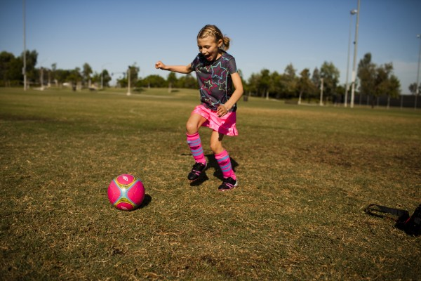Girl playing with soccer ball on the field