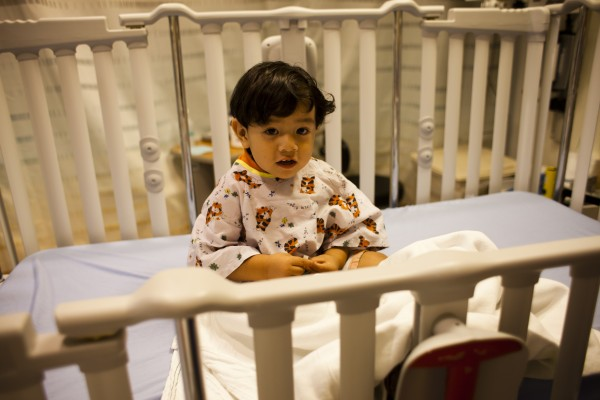 young patient sitting in crib