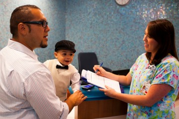 Nurse with dad and son in the reception area