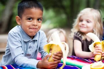 Girl and boy eating bananas