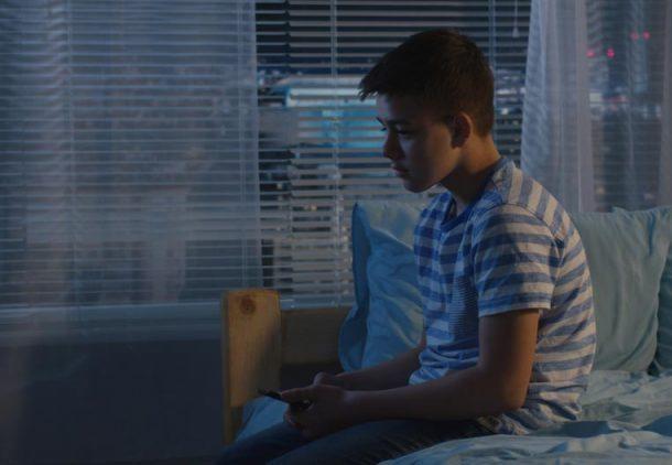 Preteen boy sits on bed in dark room