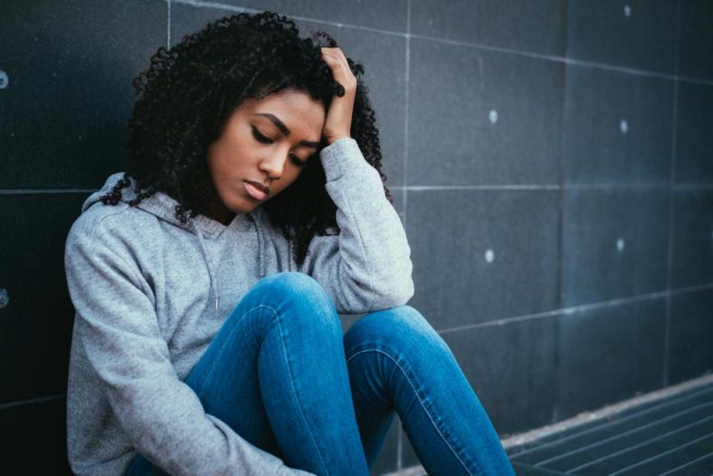 Teenage girl sits against wall looking stressed