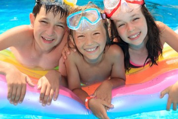 Three kids with goggles in the pool
