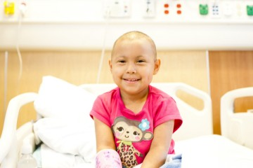 Cancer patient sitting on her hospital bed