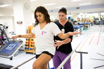 Teen girl trying to balance during rehabilitation therapy