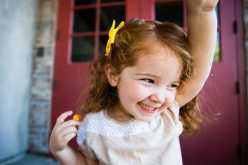 Smiling toddler girl with arm raised