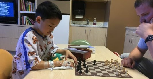 Boy playing chess game with dad in hospital playroom