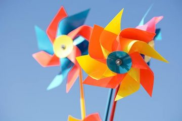 Colorful whirligigs against a blue sky