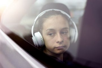 Sad girl wearing headphones staring out car window