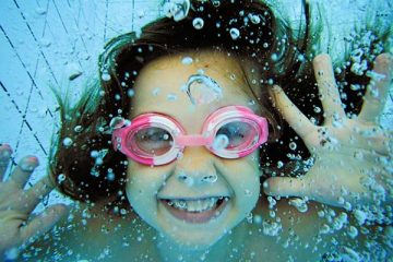 Girl underwater in pool with pink goggles