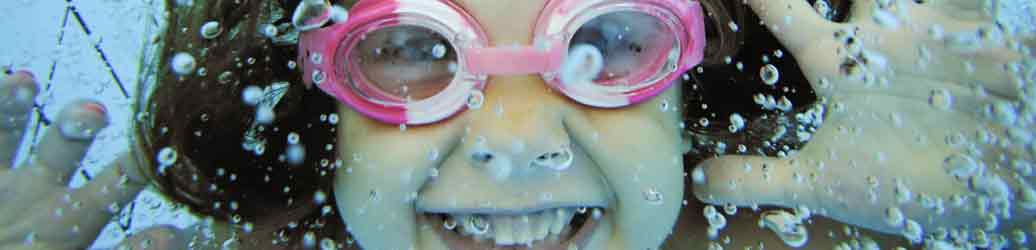 Girl in the water wearing pink goggles