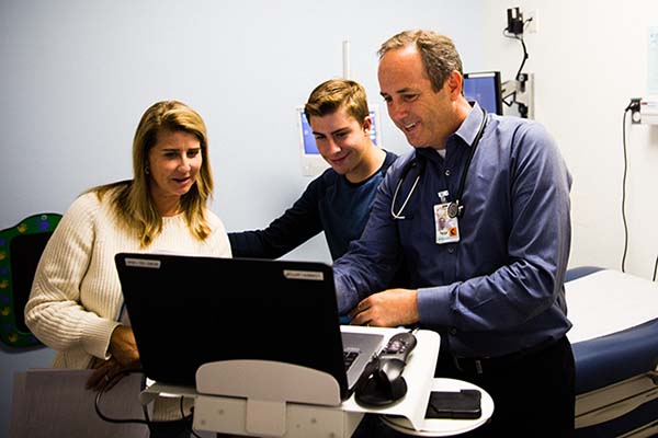 Physician looking at computer screen with mom and her son