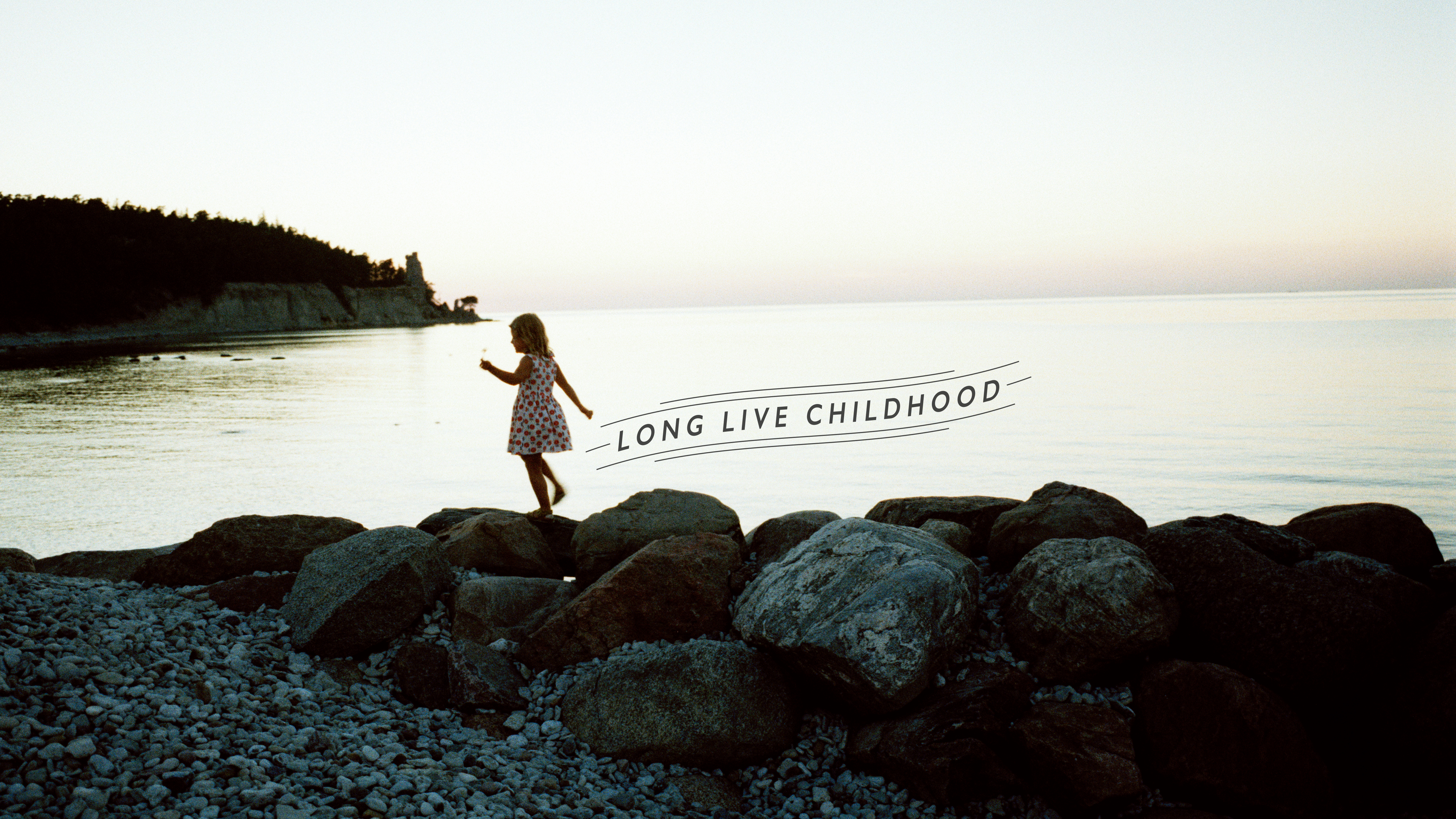 Girl on the rocks at the shore - Long Live Childhood