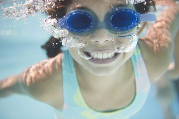 Girl with blue goggles in the water