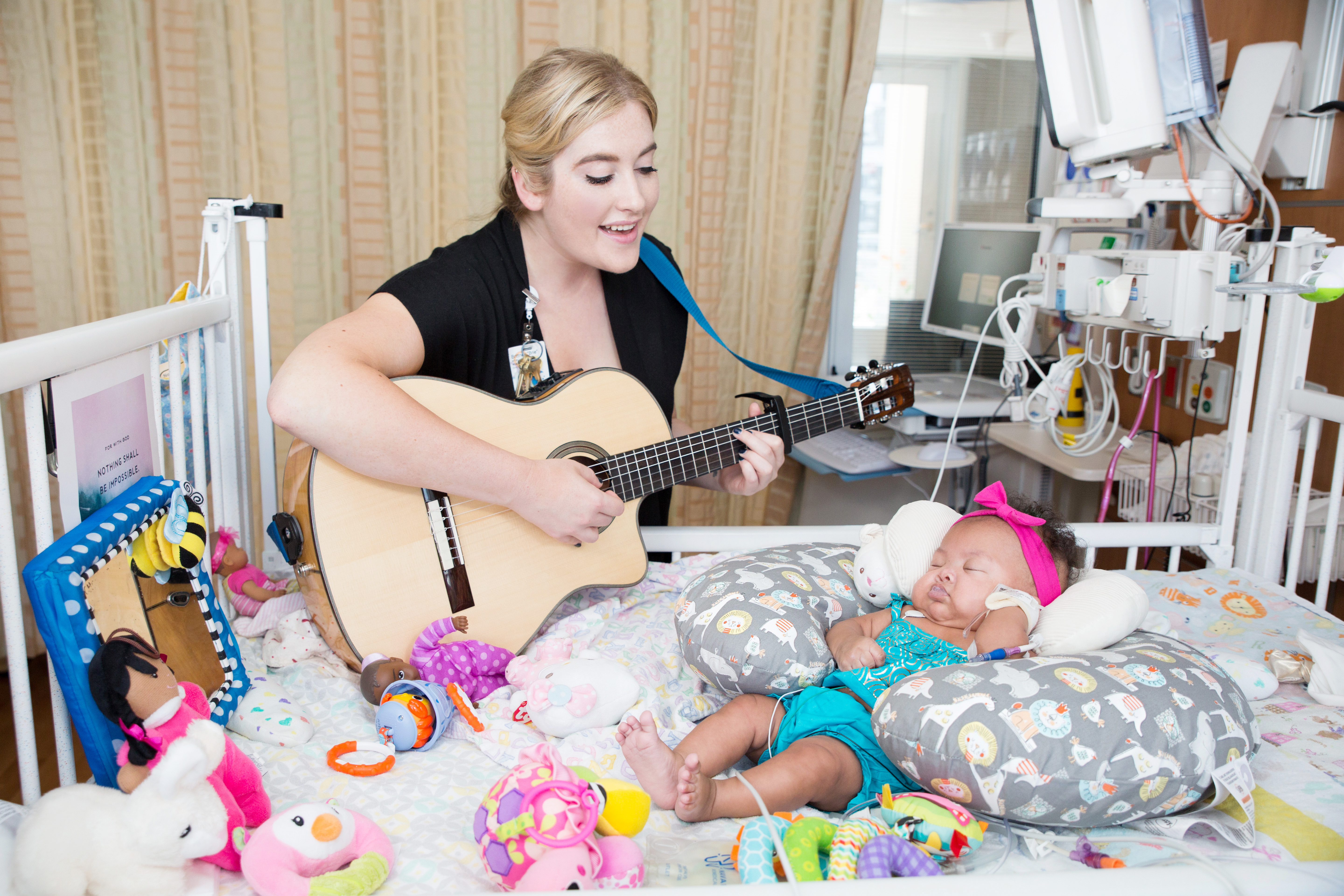 Music therapist with guitar singing to patient