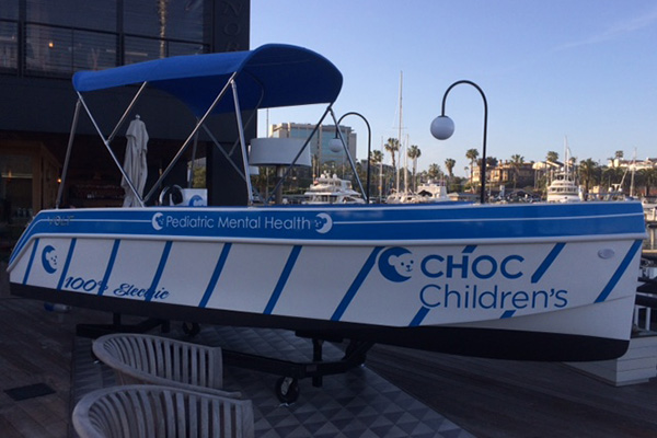 Boat in harbor with CHOC Children's brand