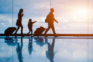 Family waking through airport terminal pulling their suitcases