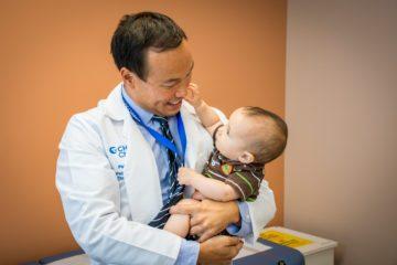 Pediatric surgeon holding child