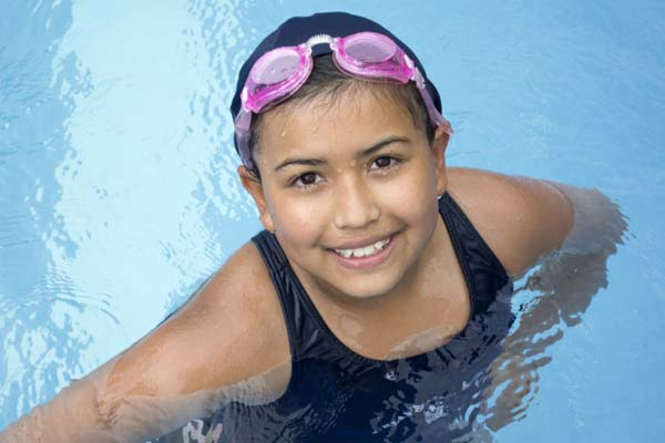 Young girl in the pool with pink goggles