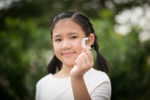 young girl holding hearing aid