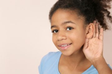 young girl holding hand against ear