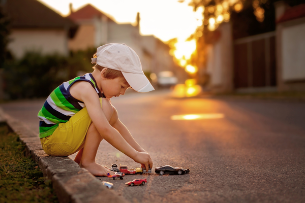 little boy wearing striped shirt and hat playing with toy cars in the street at sunset