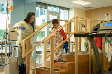 young boy wearing cape and hospital gown walking stairs with physical therapist