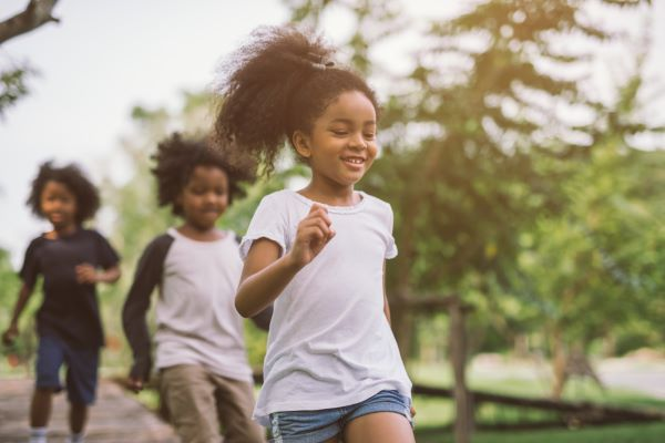 young girl running in the park with friends