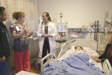 Providers consulting at bedside of CVICU patient and mom