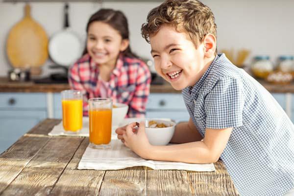 Two smiling kids eating breakfast
