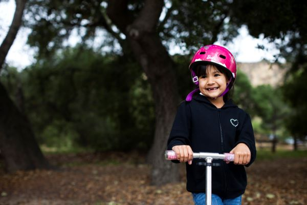 young girl wearing helmet and riding scooter