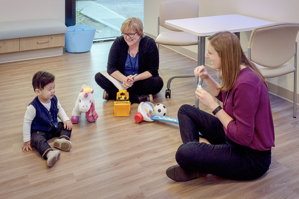 Toddler boy with doctor and psychologist for assessment