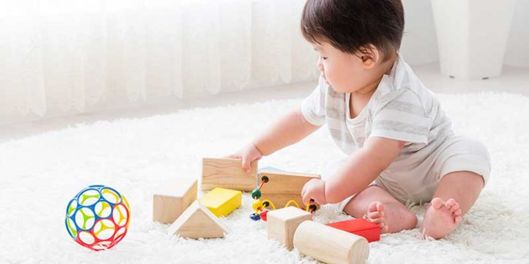 Toddler playing with toys on a white rug