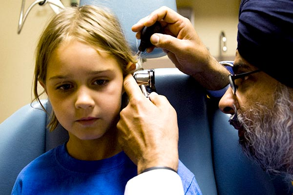 Physician looking into boy's ear