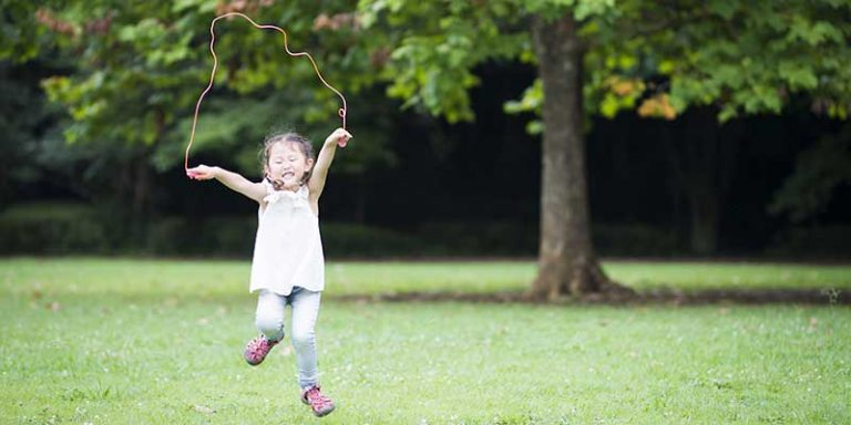 Young girl skipping rope in a park