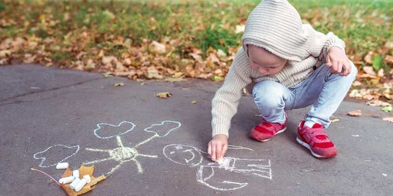 Young child drawing with chalk on a sidewalk