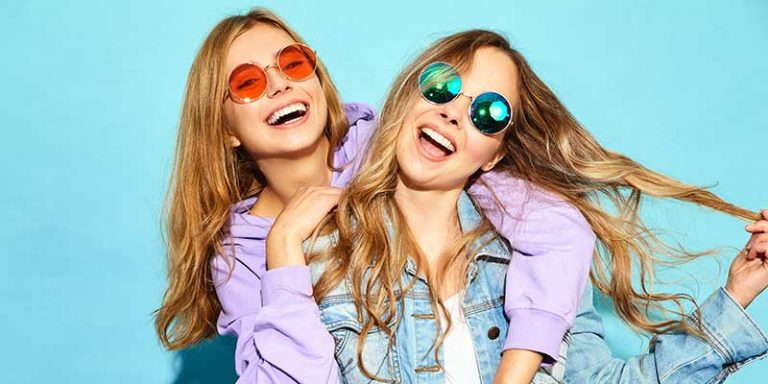 two teen girls smiling and having fun in front of a blue wall